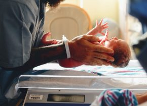 doctor putting baby on scale
